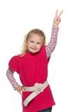 La bambina graziosa mostra il segno di vittoria Fotografie Stock Libere da Diritti