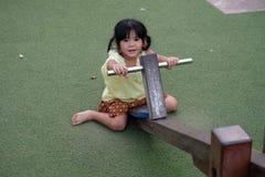 La bambina graziosa si è vestita in tailandese sul movimento alternato all'aperto in campo da giuoco Fotografia Stock Libera da Diritti