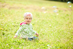 La bambina graziosa sta sedendosi sull'erba Fotografia Stock