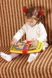 La bambina guarda nel libro Immagini Stock Libere da Diritti