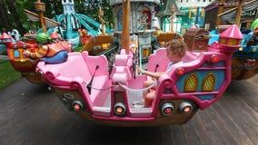 La bambina guida un carosello Parco delle attrazioni stock footage