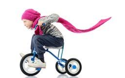 La bambina guida una bicicletta su bianco Fotografie Stock
