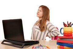 La bambina ha dolore alla schiena mentre per mezzo di un computer portatile Fotografia Stock