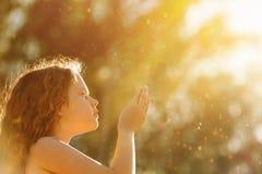 La bambina ha piegato la suoi mano e pregare immagini stock libere da diritti