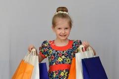 La bambina, il compratore tiene i sacchetti della spesa colorati Fotografia Stock