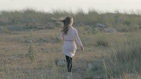 La bambina irritata sola con un giocattolo della peluche in sua mano parte nel campo al tramonto archivi video