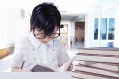 La bambina legge i libri sullo scrittorio a casa Immagine Stock