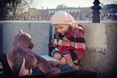 La bambina legge il libro ad un orso del giocattolo Fotografia Stock