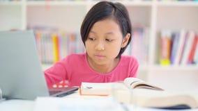 La bambina legge il libro mentre per mezzo del computer portatile archivi video