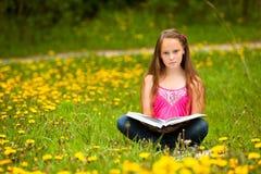 La bambina legge un libro nel prato Fotografie Stock Libere da Diritti
