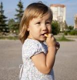 La bambina mangia il bagel Immagine Stock