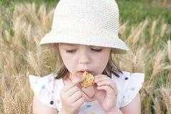 La bambina mangia il biscotto sull'aria aperta Fotografia Stock
