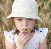 La bambina mangia il biscotto sull'aria aperta Immagini Stock Libere da Diritti