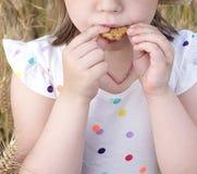 La bambina mangia il biscotto sull'aria aperta Immagine Stock