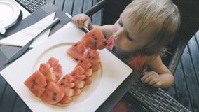 La bambina mangia l'anguria affettata stock footage