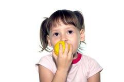 La bambina mangia la frutta gialla Fotografia Stock Libera da Diritti