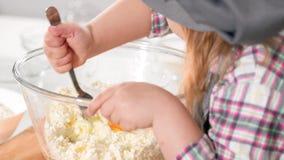 La bambina mette l'uovo in pasta per i pancake della ricotta a cucinare lo studio video d archivio