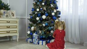 La bambina mette un regalo sotto l'albero del nuovo anno archivi video