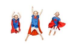 La bambina molto emozionante si è vestita come il salto dell'eroe isolata su fondo bianco Fotografia Stock