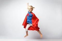 La bambina molto emozionante si è vestita come il supereroe che salta accanto alla parete bianca Immagine Stock