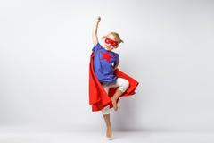 La bambina molto emozionante si è vestita come il supereroe che salta accanto alla parete bianca Fotografia Stock