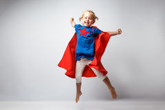 La bambina molto emozionante si è vestita come il supereroe che salta accanto alla parete bianca Fotografia Stock Libera da Diritti