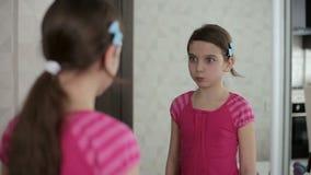 La bambina mostra i fronti davanti ad uno specchio video d archivio