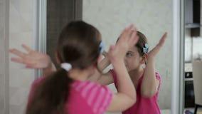 La bambina mostra i fronti davanti ad uno specchio stock footage