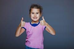 La bambina mostra il segno 'sì' dita su gray Fotografia Stock