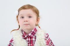 La bambina negli smorfie della maglia della pelliccia e distoglie lo sguardo Immagini Stock