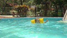 La bambina nuota in stagno vicino all'acquascivolo contro le piante video d archivio
