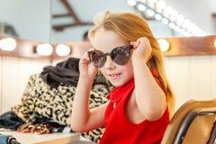 La bambina in occhiali da sole si avvicina allo specchio fotografia stock libera da diritti