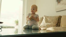 La bambina ottiene sulla tavola e prende la mela verde su stanza in appartamento stock footage