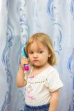 La bambina pettina i capelli una spazzola per i capelli Fotografie Stock Libere da Diritti