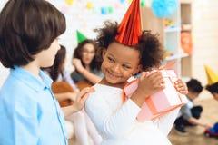 La bambina piacevole in vestito bianco è soddisfatta con il regalo che è stata data dal ragazzo in camicia blu al compleanno immagine stock libera da diritti
