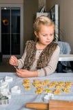 La bambina produce i biscotti Fotografie Stock