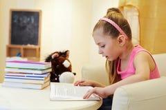 La bambina ricopre con canne il libro che si siede in grande poltrona Fotografie Stock