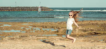 La bambina salta su una spiaggia Fotografia Stock Libera da Diritti