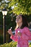 La bambina salta una bolla e le meraviglie esso Fotografia Stock