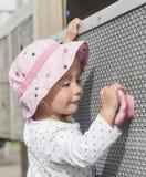 La bambina scala entusiasta l'ostacolo sul campo da giuoco immagine stock