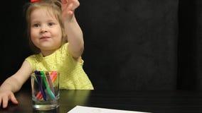 La bambina sceglie una matita rossa mentre disegna stock footage