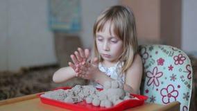 La bambina scolpisce le figure dalla sabbia archivi video