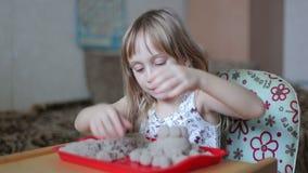 La bambina scolpisce le figure dalla sabbia stock footage