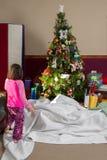 La bambina scopre il Natale coperto regali di Natale Morni Fotografia Stock Libera da Diritti