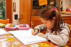 La bambina scrive con la matita sugli esercizi del taccuino Immagini Stock