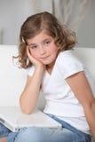 La bambina si è seduta con il computer portatile Fotografia Stock