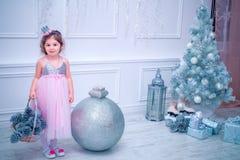 La bambina si è vestita in bello vestito dal fiore bianco di modo che posa vicino all'albero di Natale Immagini Stock