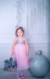 La bambina si è vestita in bello vestito dal fiore bianco di modo che posa vicino all'albero di Natale Fotografie Stock