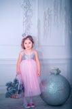 La bambina si è vestita in bello vestito dal fiore bianco di modo che posa vicino all'albero di Natale Fotografia Stock