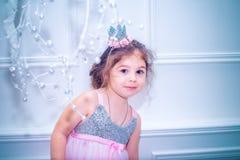 La bambina si è vestita in bello vestito dal fiore bianco di modo che posa vicino all'albero di Natale Immagine Stock Libera da Diritti